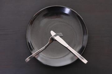 黒い木製テーブルに置かれた黒い皿とカトラリーによる不満足の合図