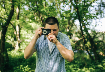 Young guy in checkered shirt is standing in the green forest with an old vintage photo camera. Hipster taking photos outdoors. Lifestyle travelling shot.