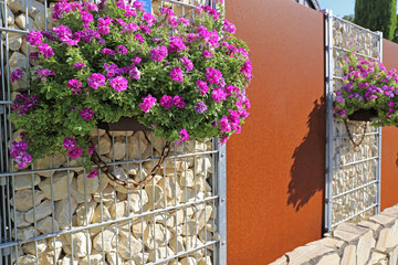 Gabione mit Sichtschutzelementen und Blumen