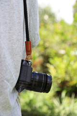 Closeup of a black camera hanging on man's shoulder with natural background in sunny day. Vertical view.