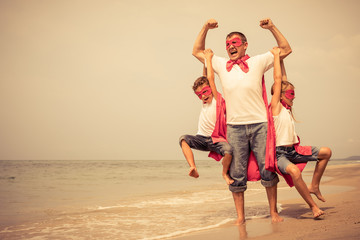 Father and children playing superhero on the beach at the day time.