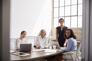 Four businesswomen look to camera,  seen from doorway