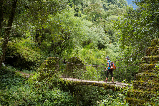 Woman backpacking across bridge in green forest of Nepal.