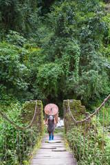 Nepali man hauling heavy metal barrel on his back across bridge in the Himalaya of Annapurna, Nepal.
