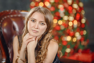 Portrait of a very pretty brunette girl at Christmas in the interiors