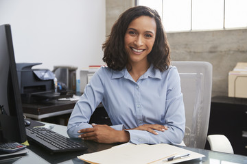 Young female professional at desk smiling to camera Wall mural