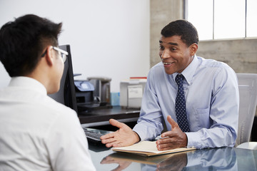 Mixed race male professional in meeting with young Asian man
