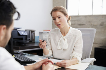 Concerned female therapist in consultation with male patient