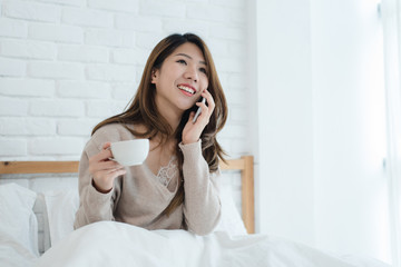 Asian woman using the smartphone on her bed while holding cup of coffee in the morning. Beautiful asian woman enjoying warm coffee and talking on telephone in her bedroom. lifestyle asia woman concept