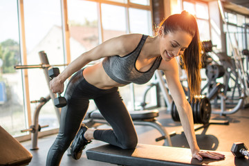 Smiling fit young woman flexing muscles with dumbbell in gym