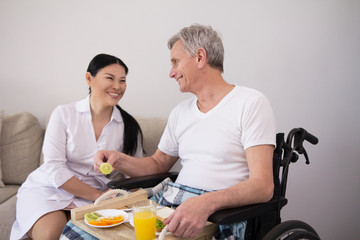 Beautiful smiling lady looking after aged disbaled man. Pretty female asian nurse laughing while talking to her disabled senior patient in wheelchair.