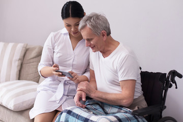 Female doctor sitting nxt to disabled man showing him pictures on phone. Friendly asian nurse shwoing something on her smartphone to elderly patient in wheelchair.