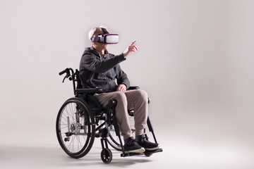Old man wearing virtual reality glasses sitting in wheelchair. Studio shot of elderly man in wheelchair with VR headset on. Isolated on solid grey background.