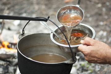 Pouring soup into a bowl with a ladle outdoor next to the fire.