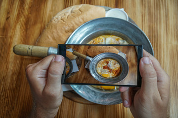 Taking Mobile Photo of Shakshuka Poached Eggs with Tomato and Bread Served in a Frying Pan. Israeli Arab Middle Eastern Cuisine. Top View
