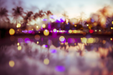 Abstract multiple-exposure bokeh view at dusk of palm trees and neon lights of Ocean Drive reflecting in puddle at dusk in South Beach, Miami, Florida, USA