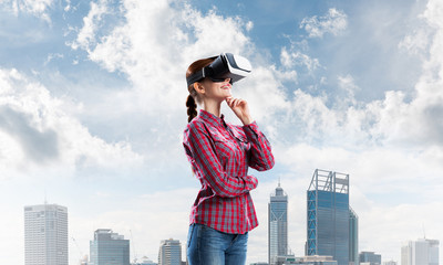 Girl in checked shirt wearing VR glasses experiencing another reality
