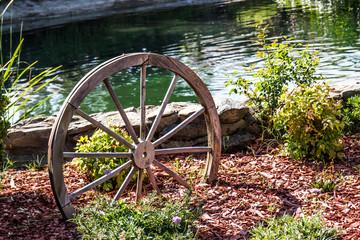Vintage Wooden Wheel In Garden Next To Pond