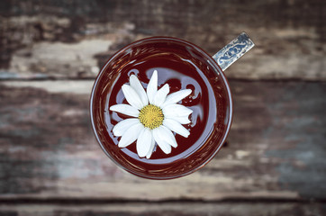 Green herbal tea with chamomile daisy petals on wooden table background.