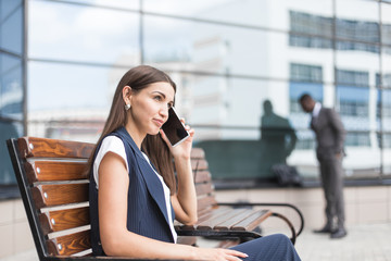 business lady in a suit is sitting at a table with a notebook, a cup of coffee and a mobile phone, against a background of glass buildings