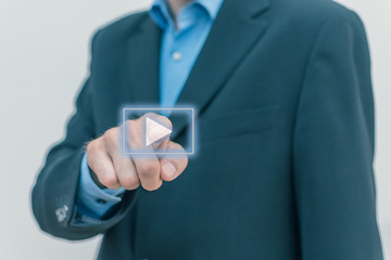 men in business suit pressing play button
