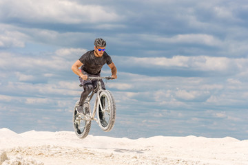 Training a bicyclist in a chalky quarry. A brutal man on a fat bike.