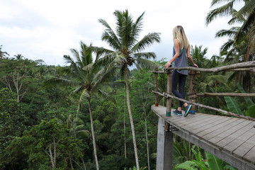 Happy active fitness girl travel concept. Young woman enjoying summer holiday and wild nature beauty in tropical jungle on Bali