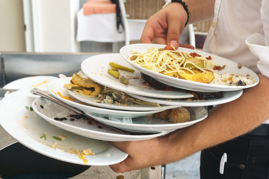 Lots of dirty plates with leftovers in their hands