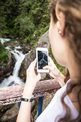 Young girl takes picture of waterfall