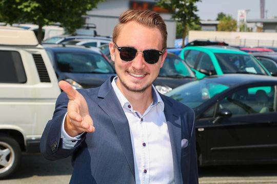 Autoverkäufer empfängt freundlich lächelnd seinen Kunden