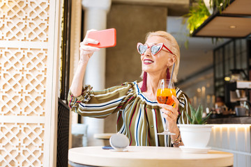 Perfect style. Cheerful good looking woman taking a selfie while holding a cocktail in her hand