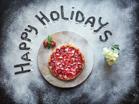 """Pizza with strawberries and the words """"happy holiday"""" made with flour on the black table."""