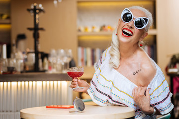 Pleasurable time. Cheerful delighted woman being in a perfect woman while enjoying her drink in the cafe
