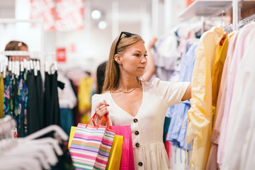 Сheerful girl in the store chooses clothes on sale