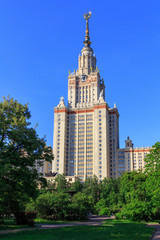 Building of Moscow State University (MSU) against blue sky and green trees in the park in sunny summer evening