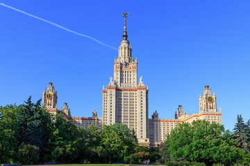 Buildings of Lomonosov Moscow State University (MSU) against blue sky and green trees in sunny summer evening
