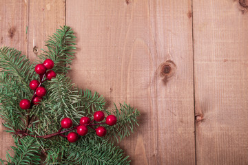 Christmas fir tree on wooden background. Red berries. Rustic style. Top view. Copy space.
