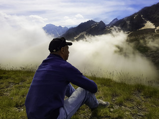 A pensive, lonely man sits on the ground in a mountain .