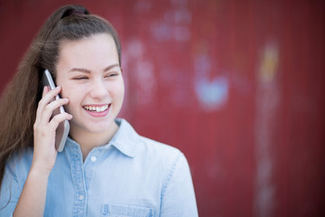 Teenage Girl Talking Outside On Mobile Phone In Urban Setting