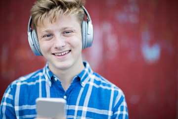 Portrait Of Teenage Boy Wearing Wireless Headphones And Listening To Music In Urban Setting