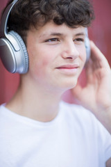 Teenage Boy Wearing Wireless Headphones And Listening To Music In Urban Setting