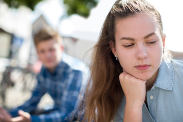 Unhappy Teenage Couple Having Argument In Urban Setting
