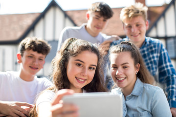 Group Of Teenagers Taking Selfie On Mobile Phone Outdoors