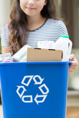 Close Up Of Teenage Girl Outside House Carrying Recycling Bin