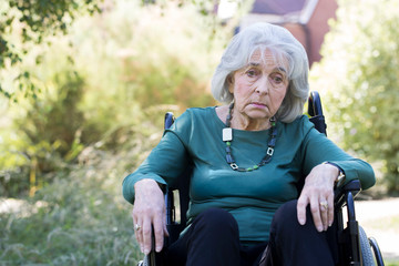 Depressed Senior Woman In Wheelchair Sitting Outdoors