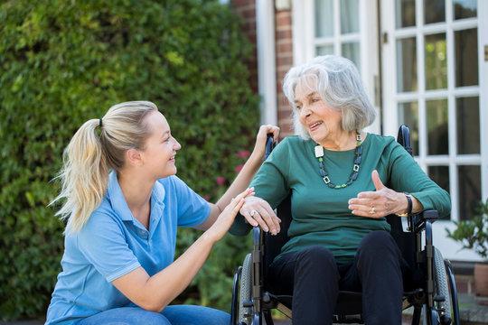 Carer Pushing Senior Woman In Wheelchair Outside Home