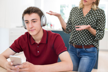 Teenage Boy Wearing Headphones And Using Mobile Phone Being Nagged By Mother At Home