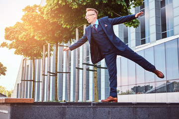 Stylish businessman dressed in an elegant suit have fun while standing outdoors against a skyscraper background.