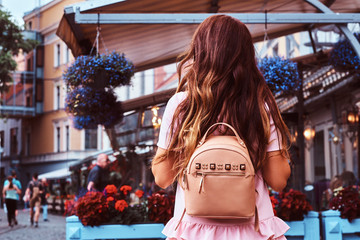 Back view of a woman with brown hair dressed in pink dress with a rucksack standing near the terrace cafe.