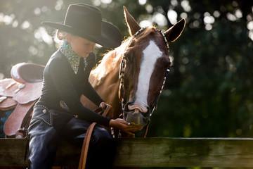 Girl with cowboy hat on feeding horse